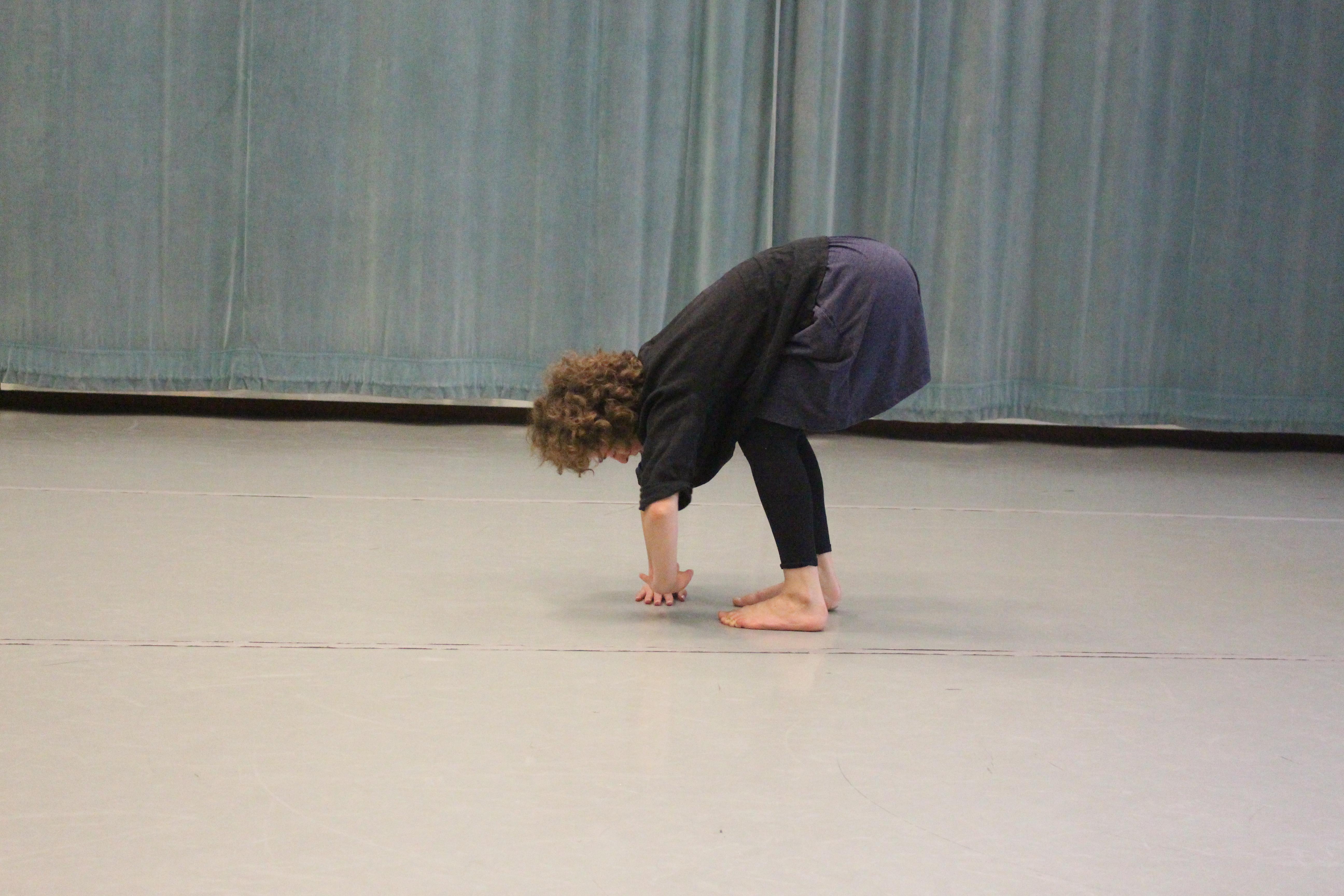 woman bent forward in dance pose